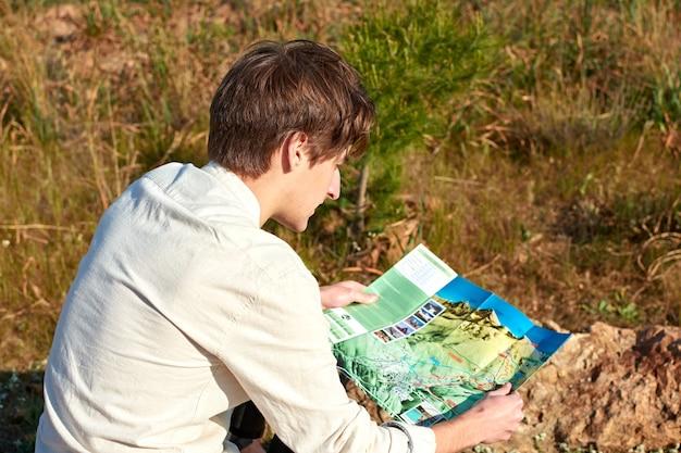 Un primo piano di un giovane esploratore spagnolo alla ricerca delle montagne osservando una mappa