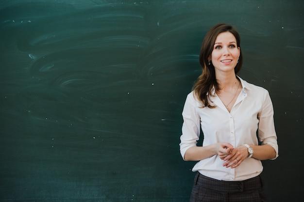Primo piano di giovane insegnante femminile contro la lavagna nella classe