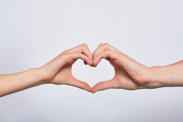 Giovani mani del primo piano che si tengono l'un l'altro