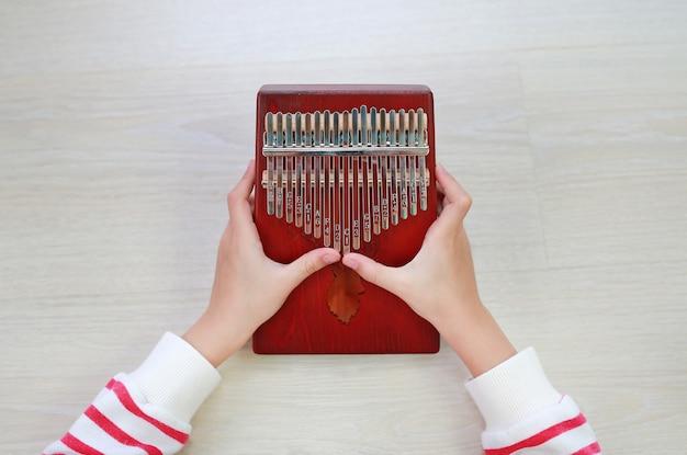 Primo piano giovani mani che giocano kalimba