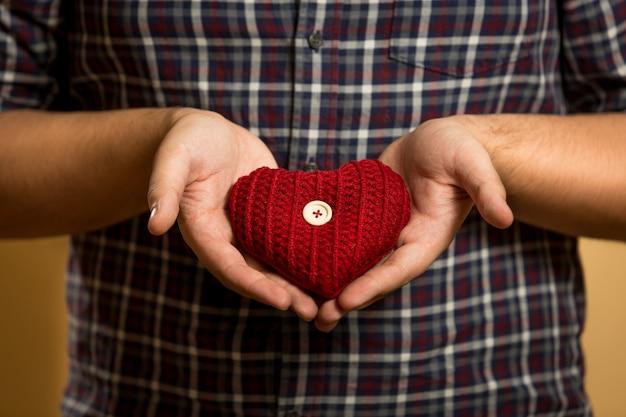 Primo piano del giovane che tiene il cuore a maglia rosso nelle mani