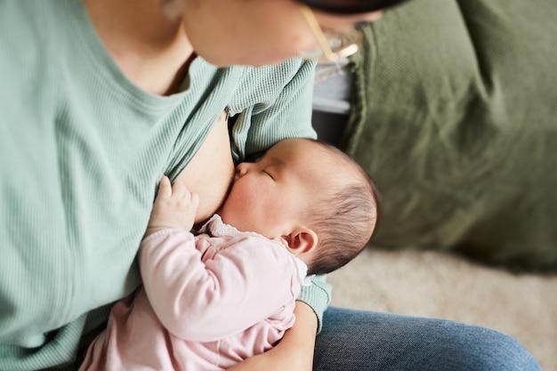 Primo piano della giovane madre che attacca il bambino al seno durante l'allattamento al seno