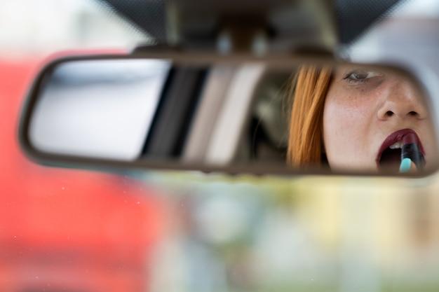 Primo piano di un giovane autista donna rossa correggendo il trucco con rossetto rosso scuro guardando nello specchietto retrovisore auto dietro il volante di un veicolo.