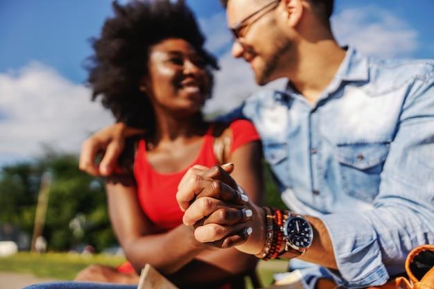 Primo piano di giovane sorridente multiculturale coppia hipster, tenendosi per mano e seduti all'aperto in una bella giornata di sole.