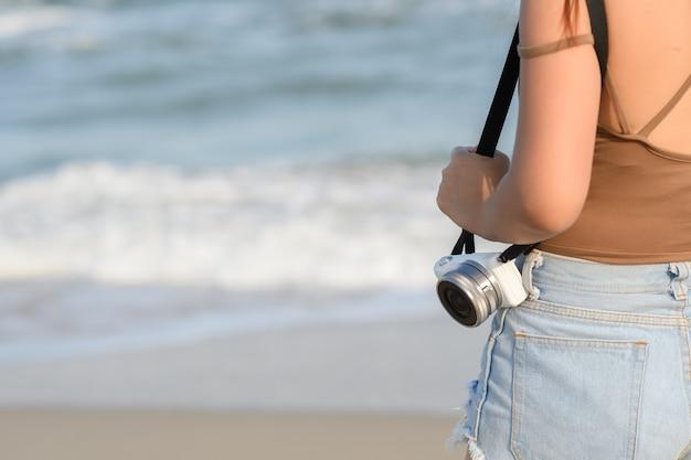 Primo piano giovane donna turistica che tiene la macchina fotografica sulla spiaggia e sul mare.
