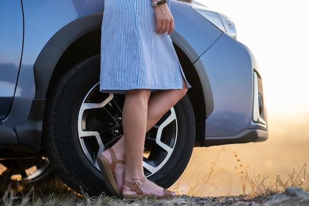 Primo piano della giovane donna in abito blu in piedi vicino al suo veicolo al tramonto. concetto di viaggio e vacanza.