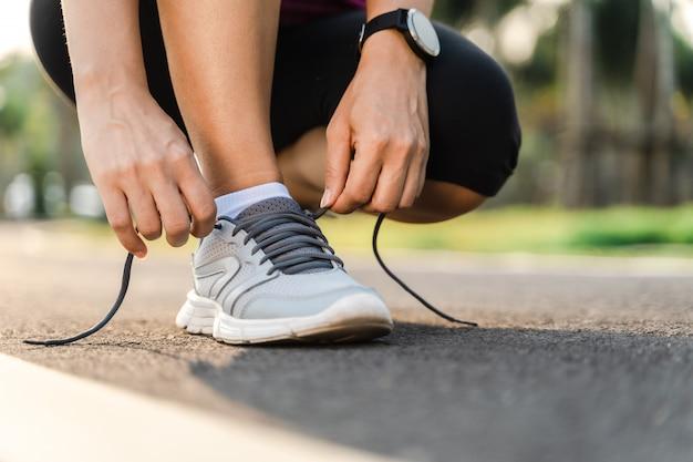 Primo piano del corridore della giovane donna che lega i suoi laccetti. concetto di salute e fitness.