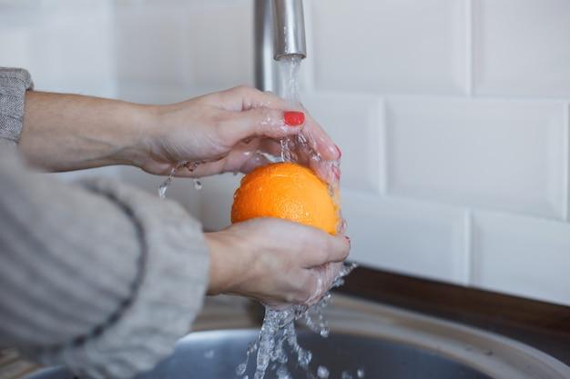Primo piano della giovane donna lava i frutti per prevenire l'infezione da coronavirus