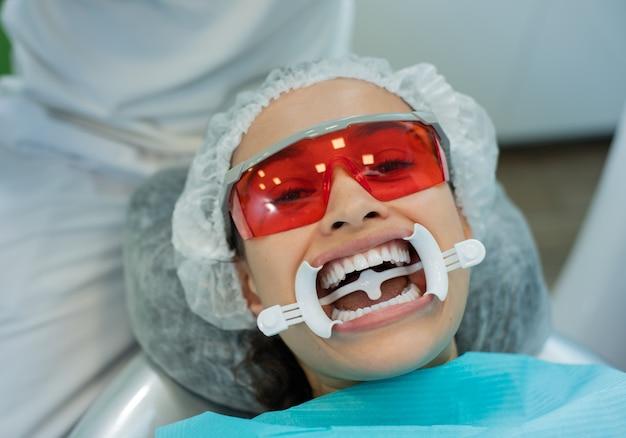 Primo piano della giovane donna che indossa la bocca divaricatore in attesa di esame orale in studio odontoiatrico.