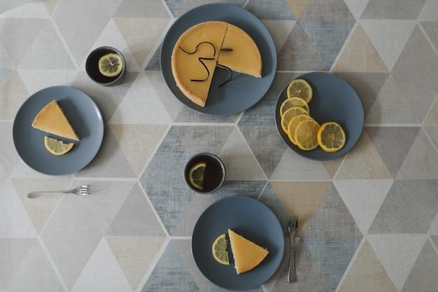 Primo piano della squisita crostata al limone con set da tè e limoni. vacanza natura morta. piatto piano della pausa tè pomeridiano girato con una torta al limone