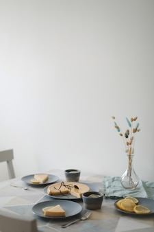 Primo piano di squisita crostata al limone con set da tè e limoni