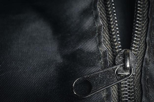 Chiusura lampo del primo piano su un oggetto d'arte sfocato dettaglio borsa nera