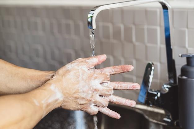 Primo piano uomo asiatico lavaggio delle mani con acqua del rubinetto in cucina a casa assistenza sanitaria di covid19