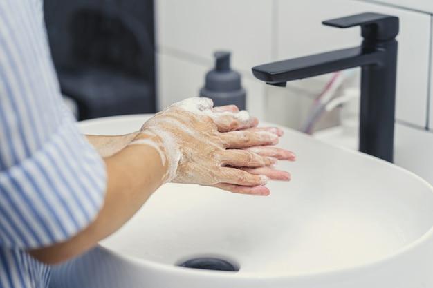 Primo piano della donna asiatica che si lava le mani con l'acqua del rubinetto nel bagno di casa