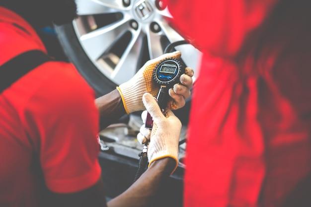 Closu sul meccanico nero che gonfia un pneumatico nella stazione di servizio. controllo pressione aria con manometro. manutenzione auto e concetto di garage di servizio auto.