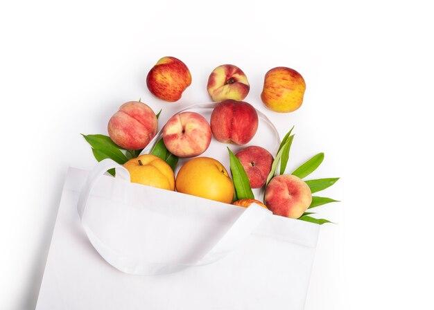 Borsa di stoffa con vari frutti sulla superficie bianca