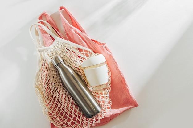 Borsa per la spesa in tessuto con tazza da caffè riutilizzabile e bottiglia d'acqua. stile di vita sostenibile.