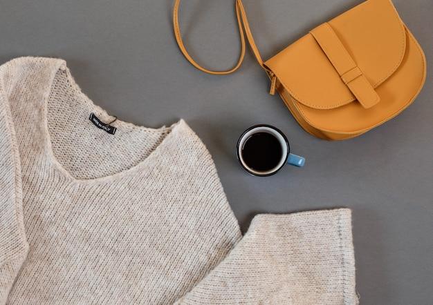 Vestiti, una tazza di caffè, una borsa da donna disposta su uno sfondo grigio vista dall'alto.