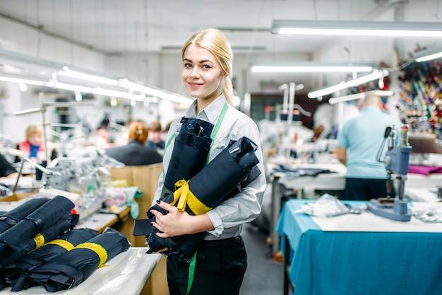 Designer di vestiti che tiene in mano materiali tessili in tessuto, fabbricazione su fabbrica di cucito. misura della curva del vestito, sarta, sartoria o sartoria