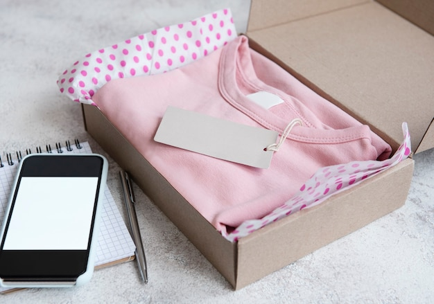 Vestiti per bambini in una scatola di cartone aperta. concetto di acquisto online. consegna dei vestiti.