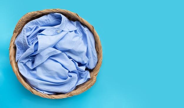 Vestiti nel cesto della biancheria su sfondo blu. copia spazio