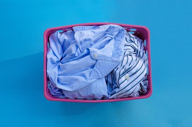 Vestiti in un cesto della biancheria sull'azzurro. copia spazio