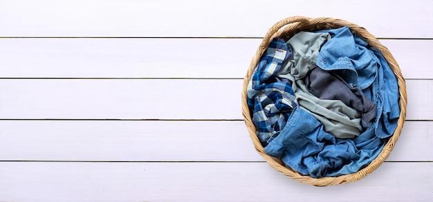 Vestiti nel canestro di lavanderia su fondo di legno bianco.