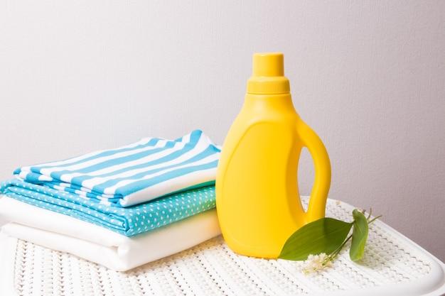 Vestiti, fiore di mughetto e ammorbidente in bottiglia senza etichetta sul cestino