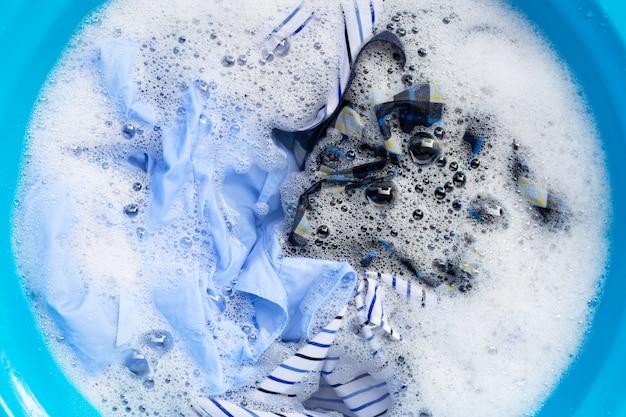 Gli indumenti immergono in acqua detergente in polvere dissoluzione. concetto di lavanderia