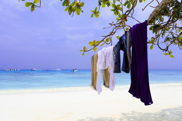 Vestiti del turismo appesi al ramo di un albero, spiaggia nel sud della thailandia