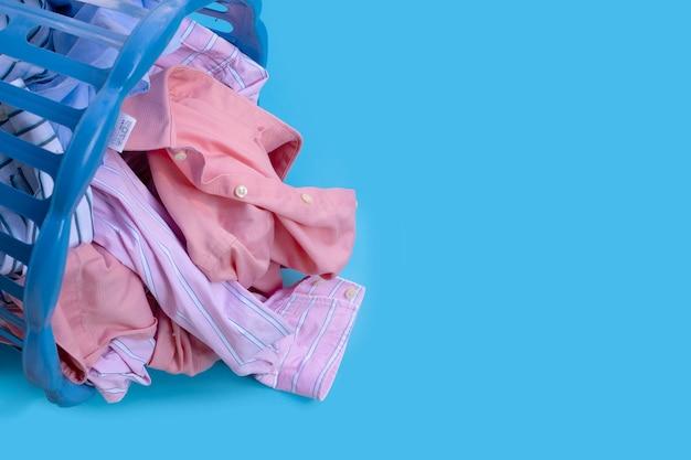 Vestiti con un cesto della biancheria sull'azzurro. copia spazio