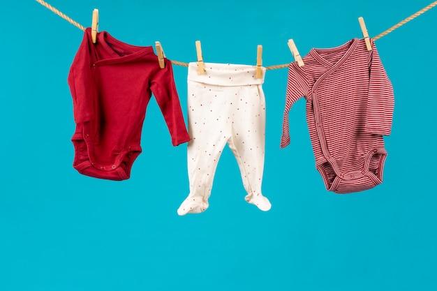 Fine del clothesline con i vestiti appuntati del bambino in su