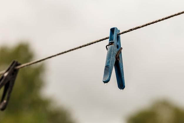 Molletta da bucato appesa a una corda. una molletta è appesa allo stendibiancheria. sfondo sfocato.