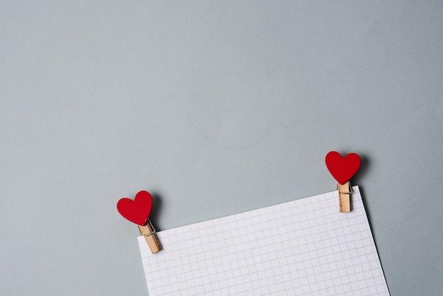 Mollette sotto forma di cuori su un foglio di carta bianco, decorazione di san valentino