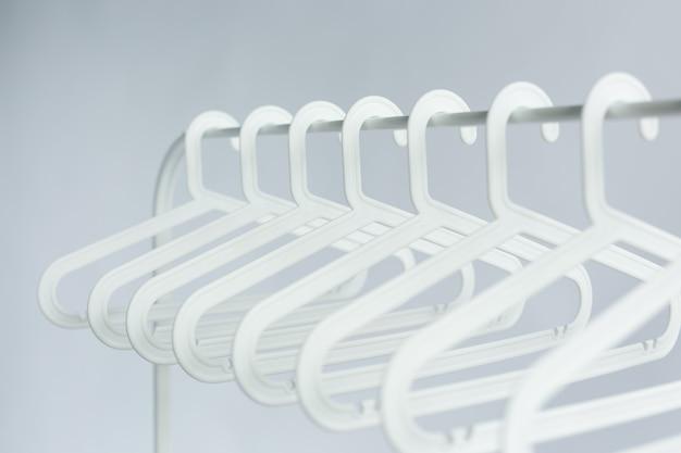 Concetto di abbigliamento, costume e accessori - appendini in plastica su un'asta sul muro bianco