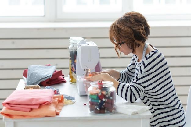 Designer di abbigliamento, sarta, concetto di persone - designer di abbigliamento che lavora nel suo studio
