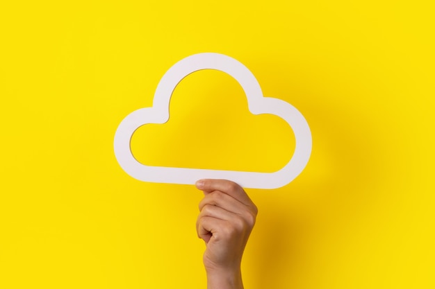 Concetto di cloud computing, mano che tiene nuvola su sfondo giallo, cloud storage
