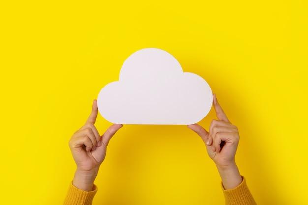Concetto di cloud computing, mani che tengono il cloud su sfondo giallo, cloud storage
