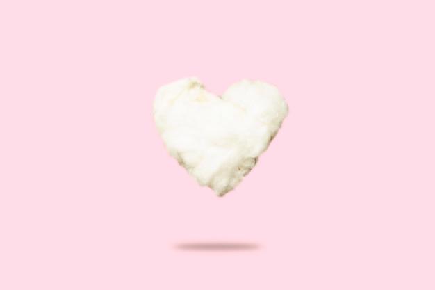 Nuvola di cotone idrofilo a forma di cuore su un rosa. concetto di amore, san valentino.