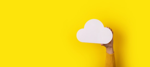 Nuvola in mano su sfondo giallo, concetto di archiviazione, immagine panoramica