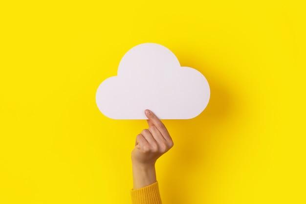 Nuvola in mano su sfondo giallo, concetto di archiviazione