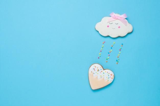 Biscotto di pan di zenzero a forma di nuvola con pioggia di cuore su sfondo blu con spazio vuoto per il testo vista dall'alto, piatto.