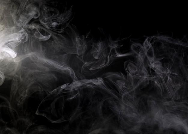 Nuvola di fumo bianco su un primo piano nero del fondo