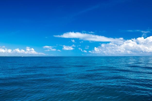 Nuvole sul cielo blu sopra il mare calmo con il riflesso della luce solare