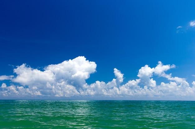 Nuvole sul cielo blu sul mare calmo con la riflessione della luce solare