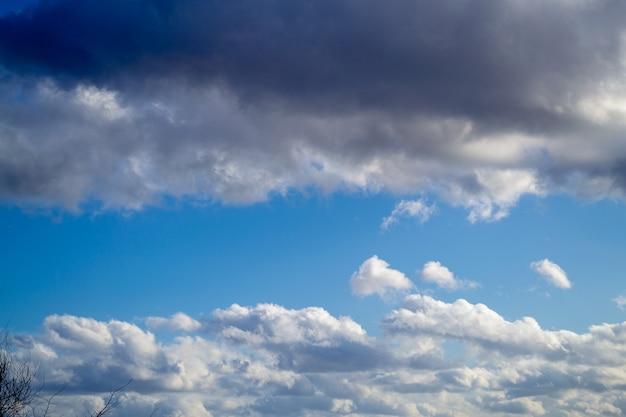 Nuvole sopra e sotto e cielo blu nel mezzo. primavera giornata di sole. bellissimo sfondo della natura.