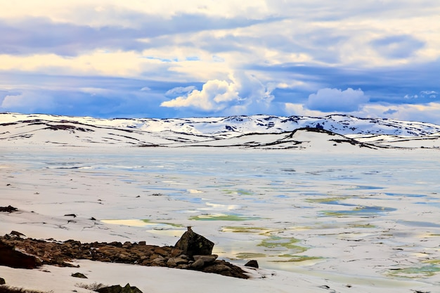 Nubi sopra le montagne innevate ghiacciate e il lago