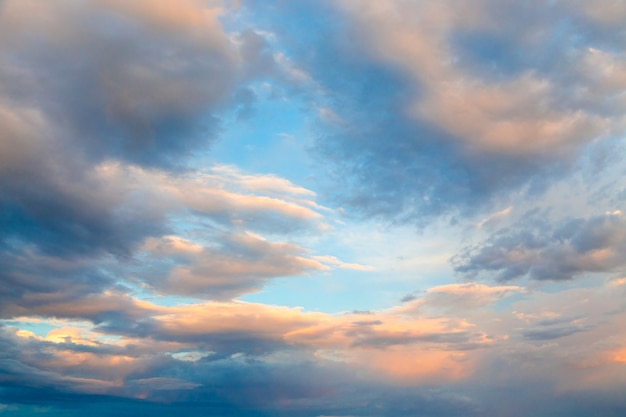 Nuvole sotto i raggi del sole al tramonto contro il cielo blu