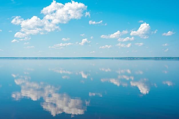 Panorama di nuvole. nuvole nel cielo blu e riflesso in un grande lago. nuvole cumuliformi bianche nel cielo sopra il paesaggio dell'acqua di mare blu, grande nuvola sopra il panorama dell'oceano, orizzonte, soleggiata giornata estiva panoramica sul