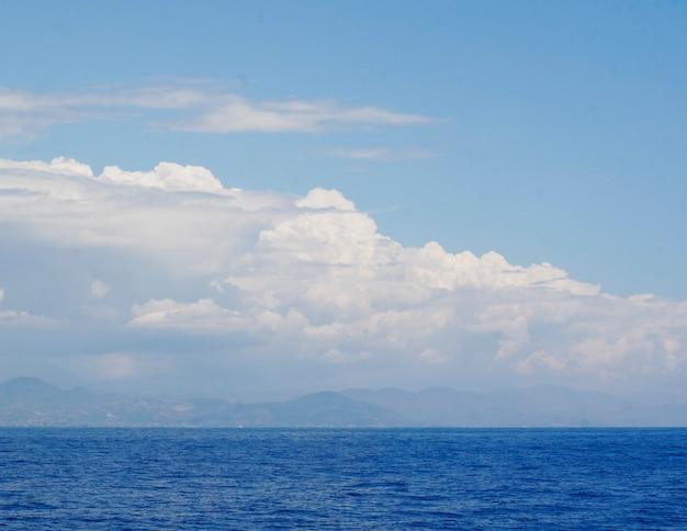 Cielo blu nuvoloso in partenza per l'orizzonte sopra una superficie blu del mare